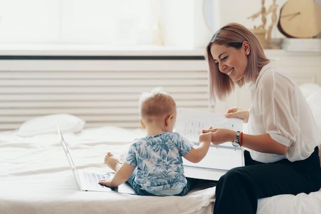 Nowożytna kobieta pracuje z dzieckiem. koncepcja wielozadaniowości, niezależności i macierzyństwa