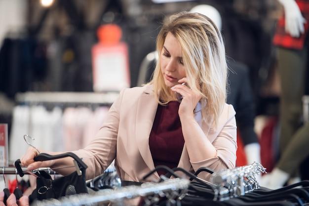 Nowożytna kobieta robi zakupy ubrania i opowiada na jej smartphone