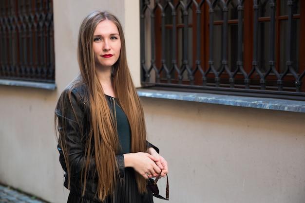 Nowożytna młoda kobieta obok biel ściany