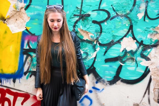 Nowożytna młoda kobieta obok graffiti ściany