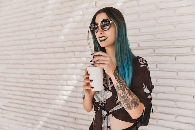 Nowożytna piękna młoda kobieta jest ubranym okulary przeciwsłonecznych trzyma rozporządzalną filiżankę