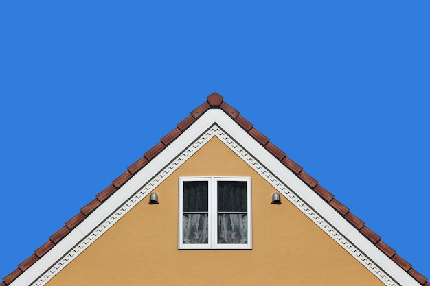 Nowożytna pomarańcze domu dachu dwuspadowego projekta ściana z jasnym niebieskiego nieba tłem.