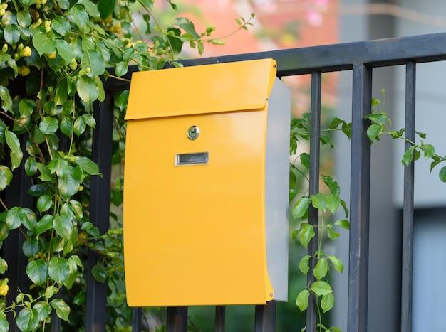 Nowożytna żółta skrzynka pocztowa na czerni ogrodzeniu z pięknym koloru żółtego tłem