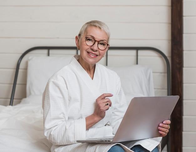 Nowożytnej smiley starsza kobieta używa laptop