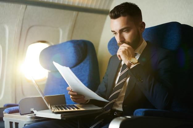 Nowożytny biznesmen pracuje w samolocie