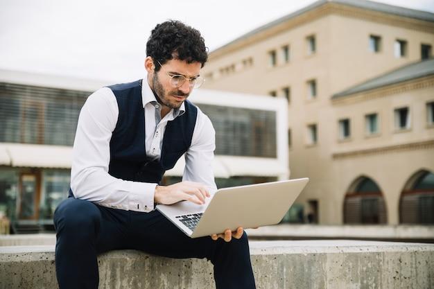 Nowożytny biznesmen używa laptop outdoors