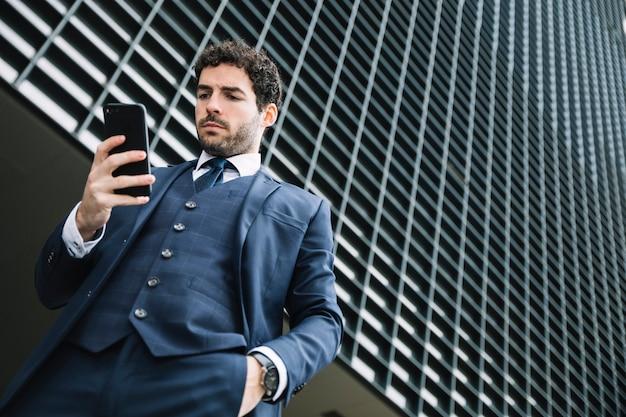 Nowożytny biznesmen używa smartphone outdoors