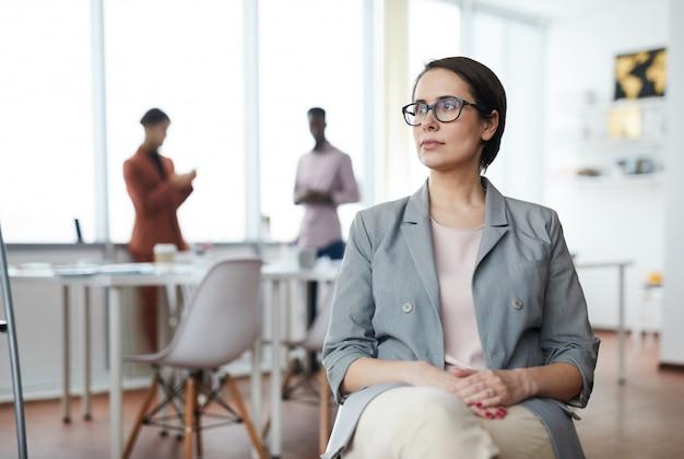 Nowożytny bizneswoman patrzeje daleko od w biurze
