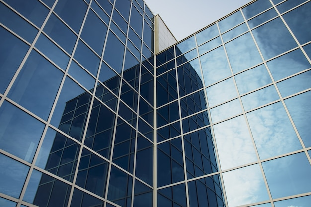 Nowożytny budynek biurowy z szklanymi okno i niebieskim niebem. tekstura wieżowca.