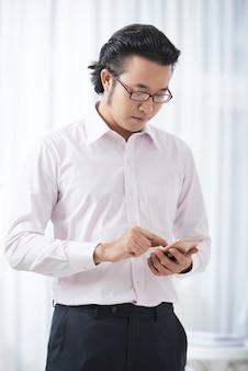 Nowożytny etniczny biznesmen używa smartphone