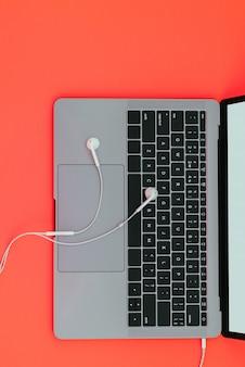 Nowożytny kruszcowy laptop i biali słuchawki odizolowywający na czerwonej powierzchni i copyspace