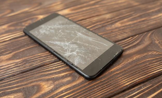 Nowożytny łamany telefon komórkowy na starym drewnianym stole