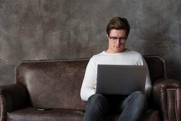 Nowożytny mężczyzna pracuje na laptopie z kopii przestrzenią