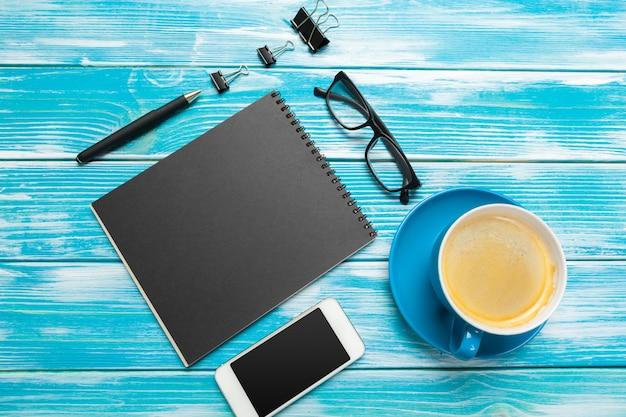 Nowożytny miejsce pracy z filiżanką kawy na drewnianym stole