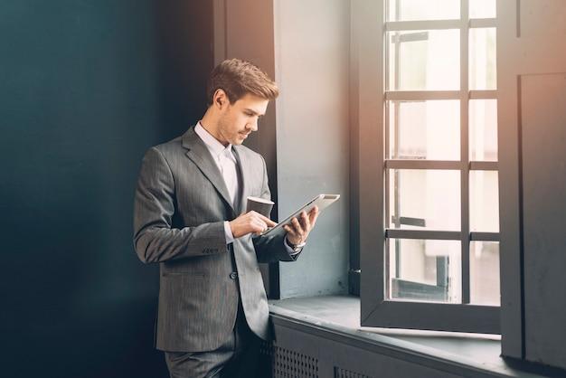 Nowożytny młody biznesmen trzyma filiżankę kawy używać cyfrową pastylkę