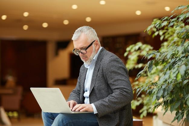 Nowożytny starszy biznesmen używa laptop