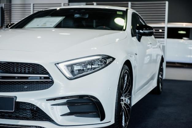 Nowy biały luksusowy nowoczesny samochód stojący wewnątrz na wystawie samochodowej. przedni widok.