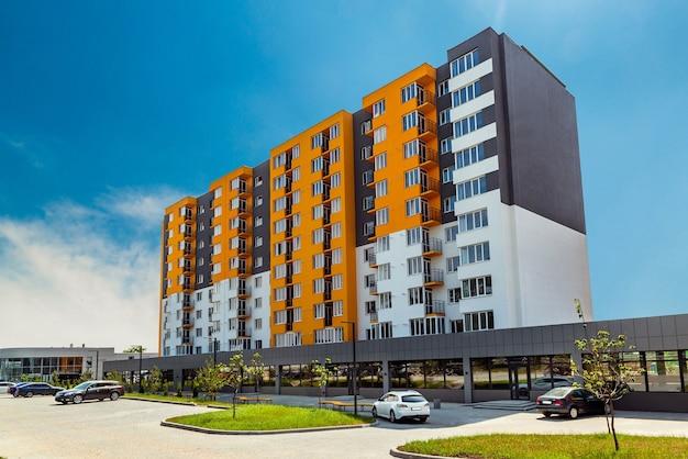 Nowy blok nowoczesnych apartamentów z balkonami i błękitnym niebem w tle