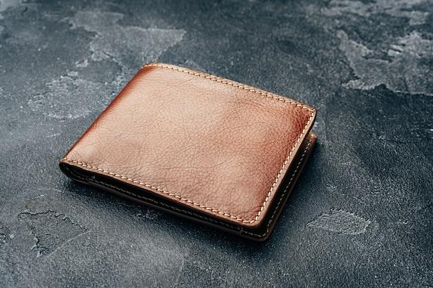Nowy brązowy skórzany portfel na ciemnym tle z bliska