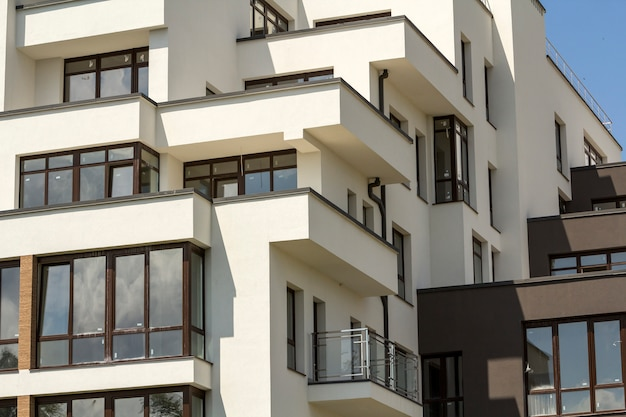 Nowy budynek mieszkalny z tarasowymi balkonami, błyszczącymi oknami i niskim płotem ochronnym na płaskim dachu.