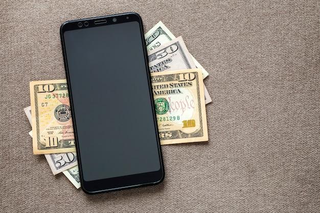 Nowy czarny nowoczesny telefon komórkowy na tle banknotów dolarów pieniędzy. nowoczesna technologia, komunikacja i handel online z wykorzystaniem koncepcji gadżetów.