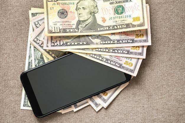 Nowy czarny nowożytny telefon komórkowy na pieniędzy dolarów banknotów tle. nowoczesna technologia, komunikacja i handel online za pomocą gadżetu.