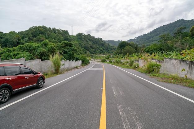 Nowy czerwony samochód suv na drodze asfaltowej z górskim zielonym lasem