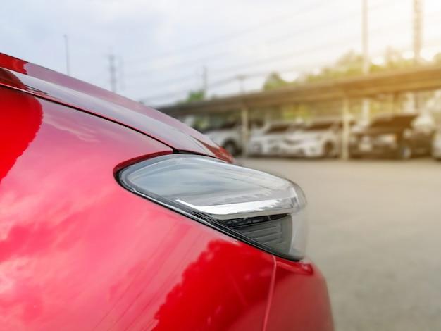 Nowy czerwony samochód w zaparkowanym z wieloma samochodami na parkingu
