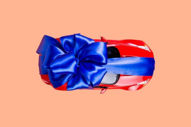 Nowy czerwony samochód z niebieskim łukiem jako prezent na koralu