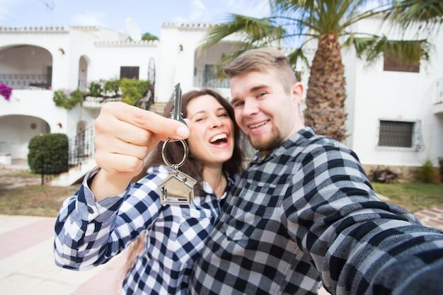 Nowy dom, nieruchomość i przeprowadzka - zabawna młoda para pokazuje klucze z nowego domu.