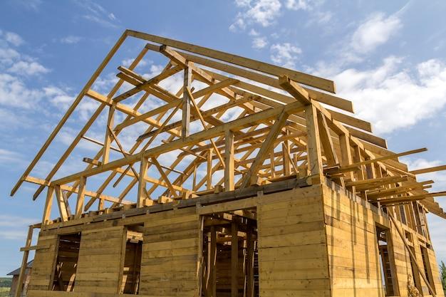Nowy domek z naturalnych ekologicznych materiałów drzewnych w trakcie budowy w zielonym polu. drewniane ściany i stroma rama dachu. nieruchomość, inwestycja, profesjonalna koncepcja budowy i przebudowy.