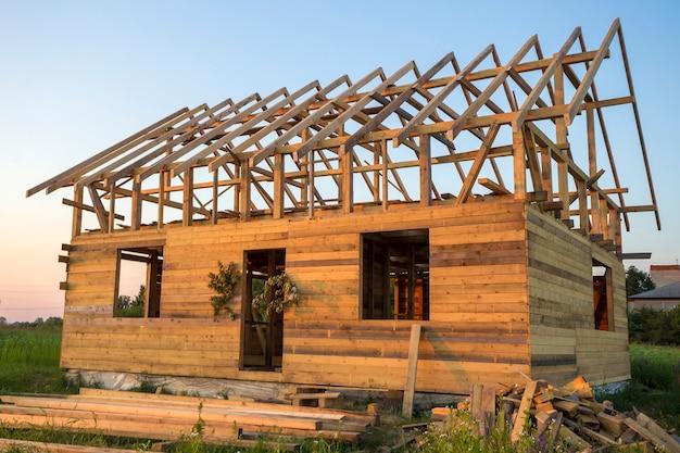 Nowy domek z naturalnych ekologicznych materiałów drzewnych w trakcie budowy w zielonym polu. drewniane ściany i stroma rama dachu.