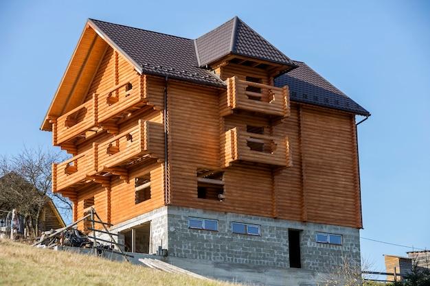 Nowy drewniany ekologiczny tradycyjny domek z naturalnych materiałów drzewnych z gontowym dachem i kamienną piwnicą w budowie w zielonej okolicy na niebieskim niebie