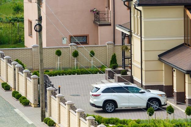 Nowy drogi biały samochód sportowy honda zaparkowany przed bramą garażową na utwardzonym, zadbanym podwórku z zielonym trawnikiem, ozdobnymi drzewami i ceglanym ogrodzeniem dużego dwupiętrowego domku. koncepcja luksusu i dobrobytu.