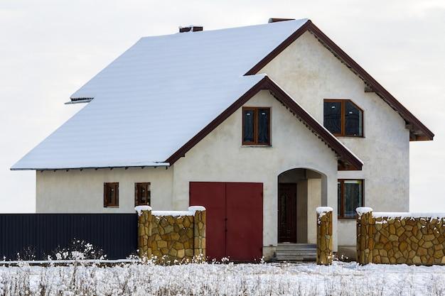 Nowy dwupiętrowy dom mieszkalny z kamiennym ogrodzeniem z przodu