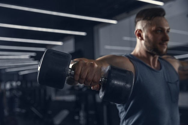 Nowy dzień władzy. młody muskularny sportowiec kaukaski ćwiczących w siłowni z ciężarami. człowiek robi ćwiczenia siłowe, trening górnej części ciała. fitness, wellness, zdrowy styl życia, koncepcja kulturystyki.