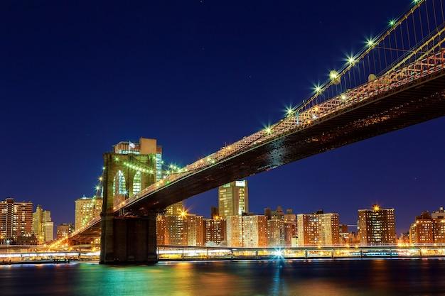 Nowy jork świeci nocą brooklyn bridge
