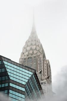 Nowy jork, usa - 03 maja 2016: empire state building. scena uliczna na manhattanie. chmura pary z metra na ulicach manhattanu w nowym jorku. typowy widok na manhattan