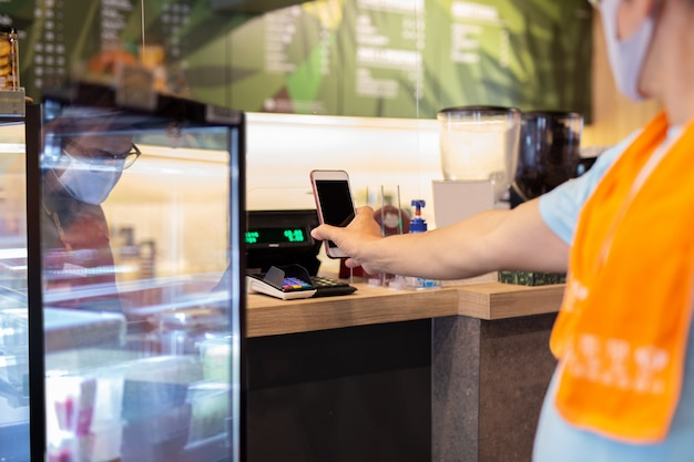 Nowy klient nomarl płacący rachunek przez telefon komórkowy z pracownikami za plastikową przegrodą w kawiarni.