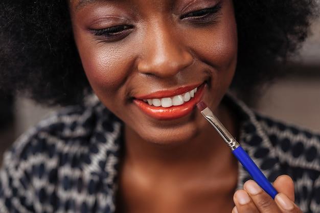 Nowy kolor szminki. niesamowita kobieta z kręconymi włosami uśmiecha się, próbując nowego koloru szminki