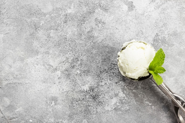 Nowy lody w łyżce na szarym tle.