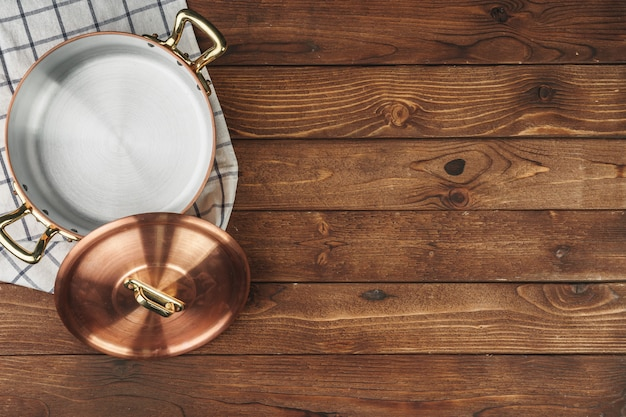 Nowy miedziany garnek do gotowania na drewnianym stole, widok z góry