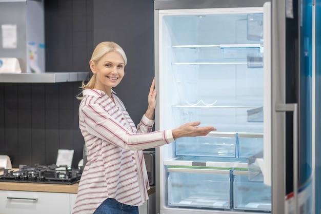 Nowy model. kobieta w koszuli w paski, demonstrując nową lodówkę w salonie