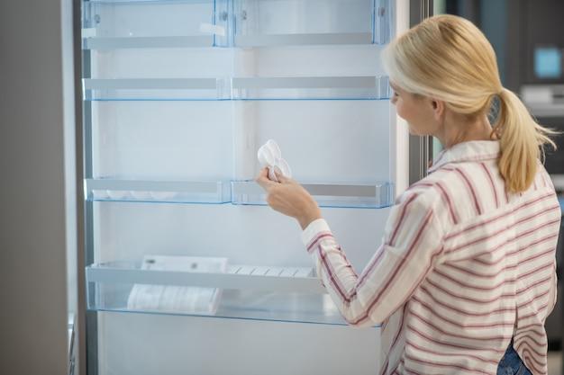 Nowy model. kobieta w pasiastej koszuli wybiera lodówkę w salonie