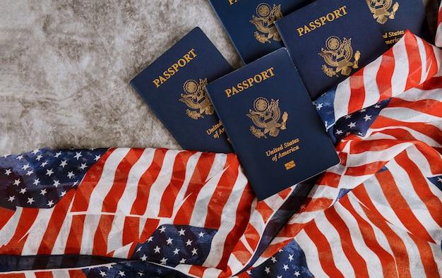 Nowy niebieski paszport stanów zjednoczonych ameryki na tle flagi usa
