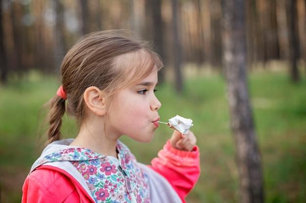 Nowy, normalny etap ucieczki, spacery na dziko przyrodzie i rodzinny wypoczynek na świeżym powietrzu. dzieci gotują i degustują pianki marshmallows smażone na ogniu, wędrówki w weekendy, styl życia
