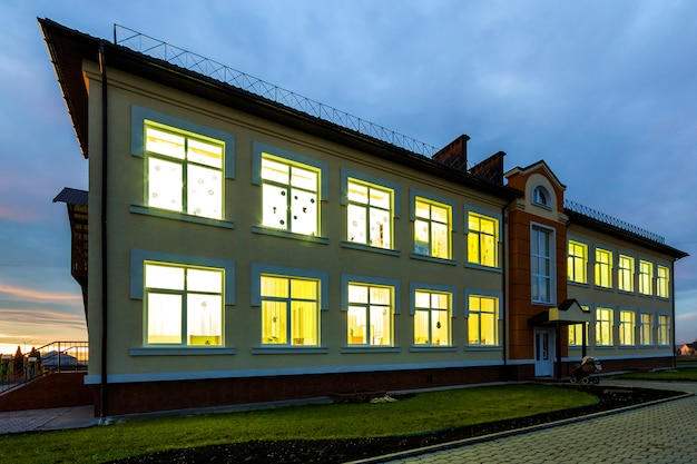 Nowy nowoczesny dwupiętrowy budynek przedszkola, zielony trawiasty trawnik i brukowane chodniki na błękitne niebo. koncepcja architektury i rozwoju.