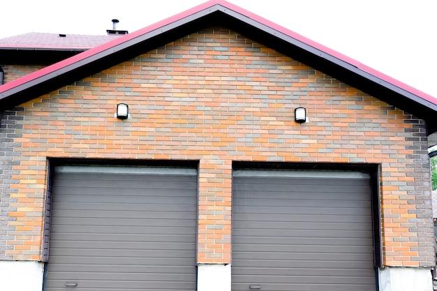 Nowy nowoczesny garaż w luksusowym mieszkalnym domu murowanym na dwa samochody z roletami na bramach.