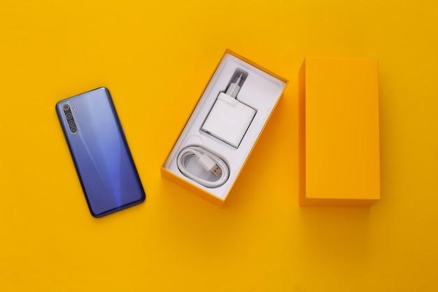 Nowy nowoczesny smartfon w pudełku do pakowania na żółto. minimalizm.