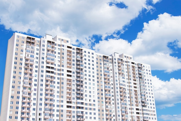 Nowy nowoczesny wielopiętrowy kompleks mieszkaniowy. niebieskie niebo z dużymi białymi chmurami